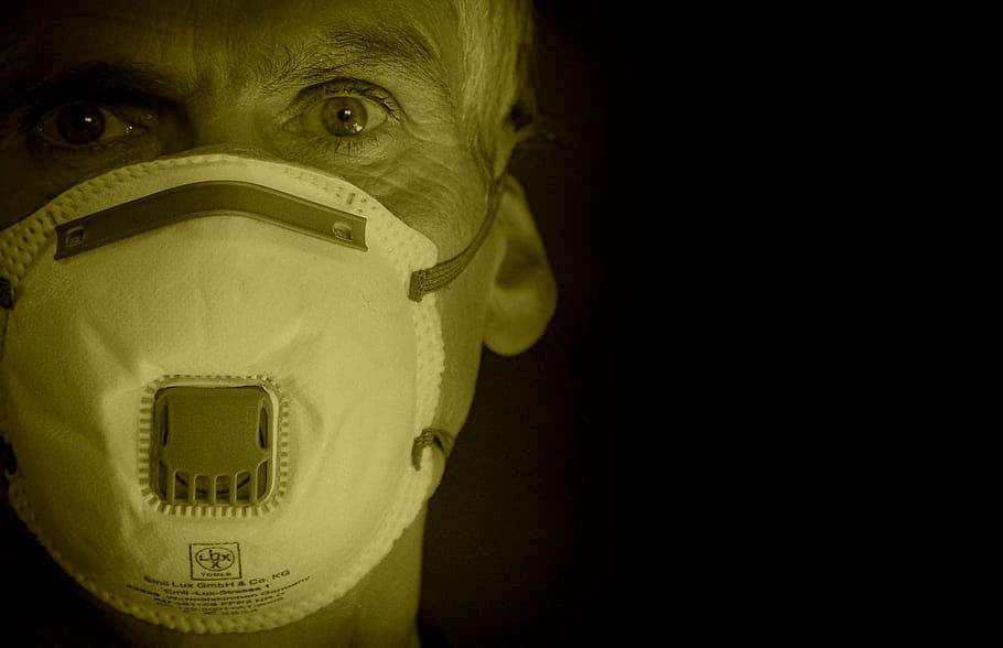 Tłumacze w czasach pandemii. Na obrazku mężczyzna w masce zasłaniającej usta i nos, patrzy w stronę czytającego.